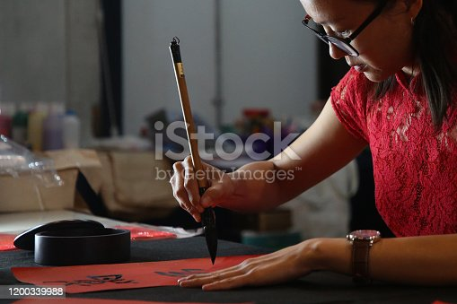 A female adult is concentrating writing Chinese calligraphy on a piece of red paper.