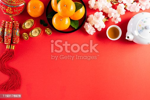 istock Chinese new year festival decorations pow or red packet, orange and gold ingots or golden lump on a red background. Chinese characters FU in the article refer to fortune good luck, wealth, money flow. 1193178928