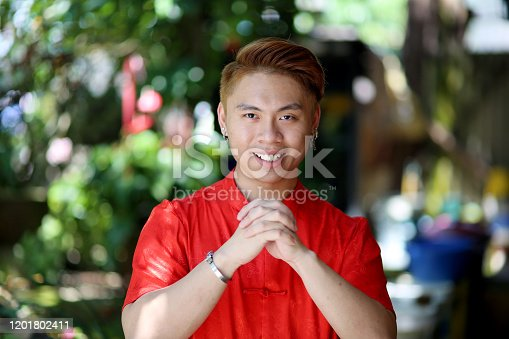 A young man is feeling cheerful with greetings hand gesture during Chinese New Year celebration in Johor, Malaysia.