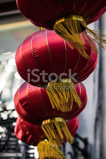 Set of red and yellow Chinese New Year lanterns hanging and blowing in the wind in San Francisco Chinatown. Focused on one with others out of focus