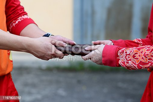 Lion dance drumsticks exchange hands from coach to junior troupe member in preparation for Chinese New Year performance in Kuala Lumpur, Malaysia.