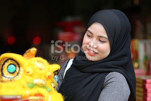 A female Muslim adult is admiring toy-sized lion dance while exploring decoration and Chinese cultures for the upcoming Chinese New Year celebration in Melaka, Malaysia.