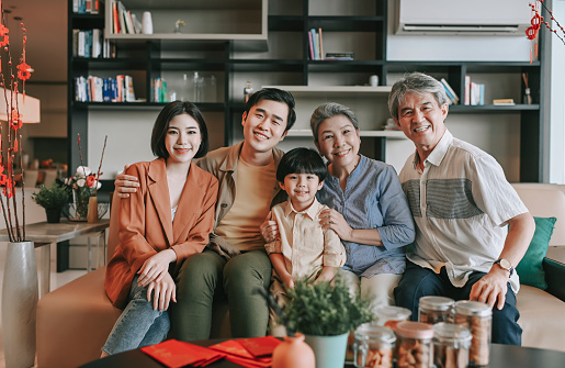 Chinese new year multi generation family sitting on sofa living room looking at camera smiling happy