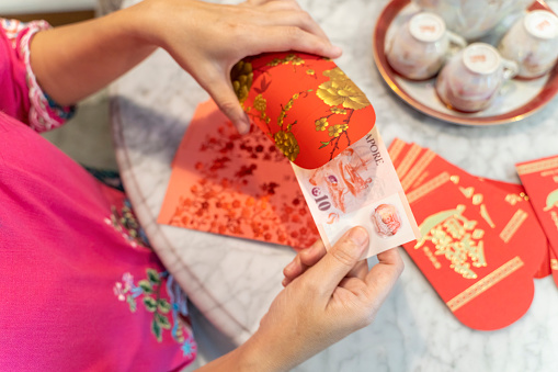 Close-up of hands preparing Chinese New Year red packets during Chinese New Year festive period  Notes to Inspector/Editor. Golden text on red packet is general Chinese greeting words for prosperity. No visible logo