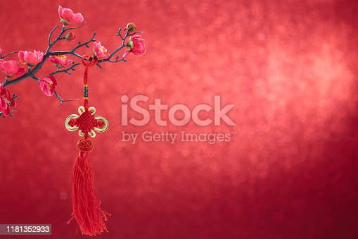 istock Chinese new year's decoration flowers plum blossoming with Chinese knot on red bokeh background 1181352933