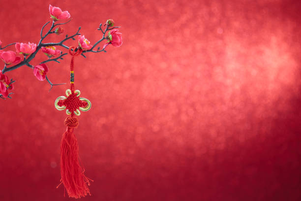 Cтоковое фото Chinese new year's decoration flowers plum blossoming with Chinese knot on red bokeh background