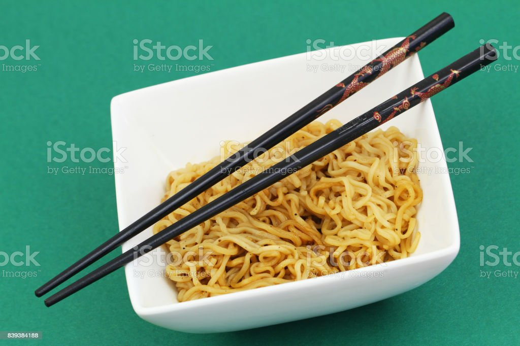 Chinese noodles in bowl and chopsticks on green background stock photo