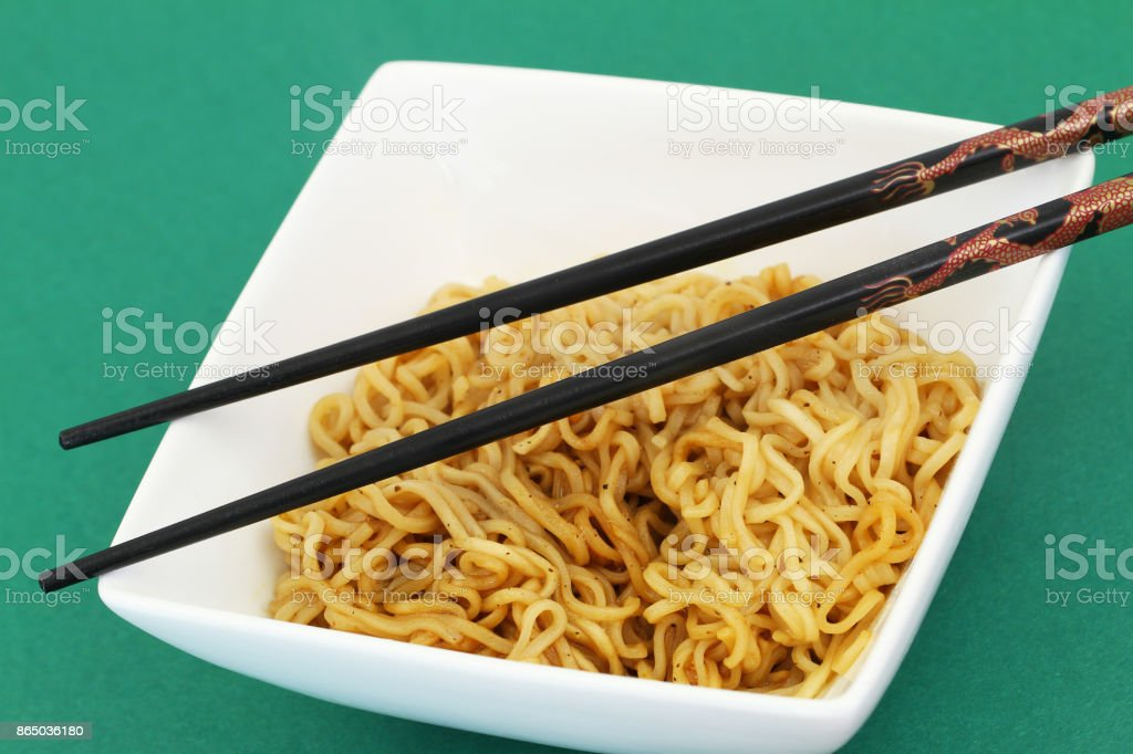 Chinese noodles in white bowl with chopsticks on top stock photo