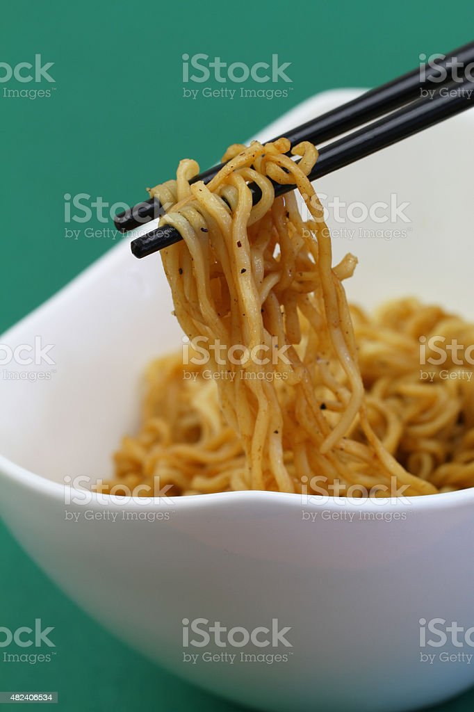 Chinese noodles on chopsticks, closeup stock photo