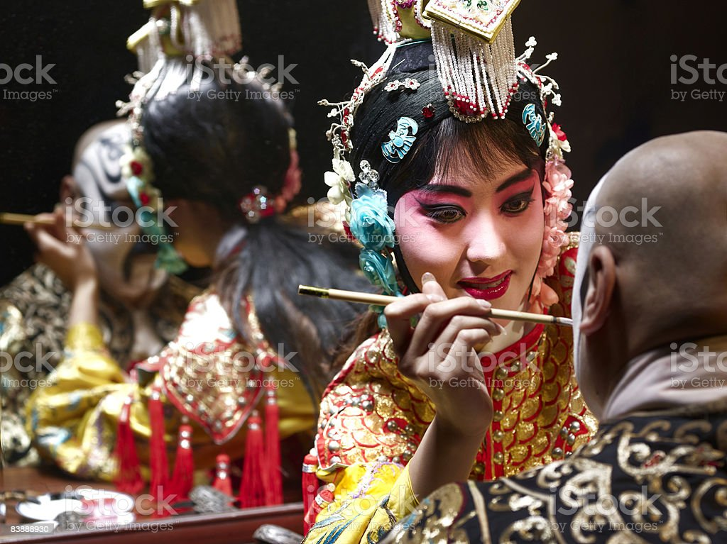 Chinese opera singer applying makeup to male royalty-free stock photo