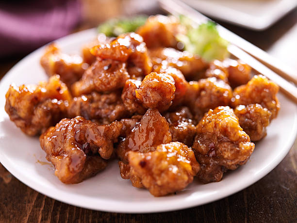 chinese orange chicken with chopsticks - chinese food stock photos and pictures