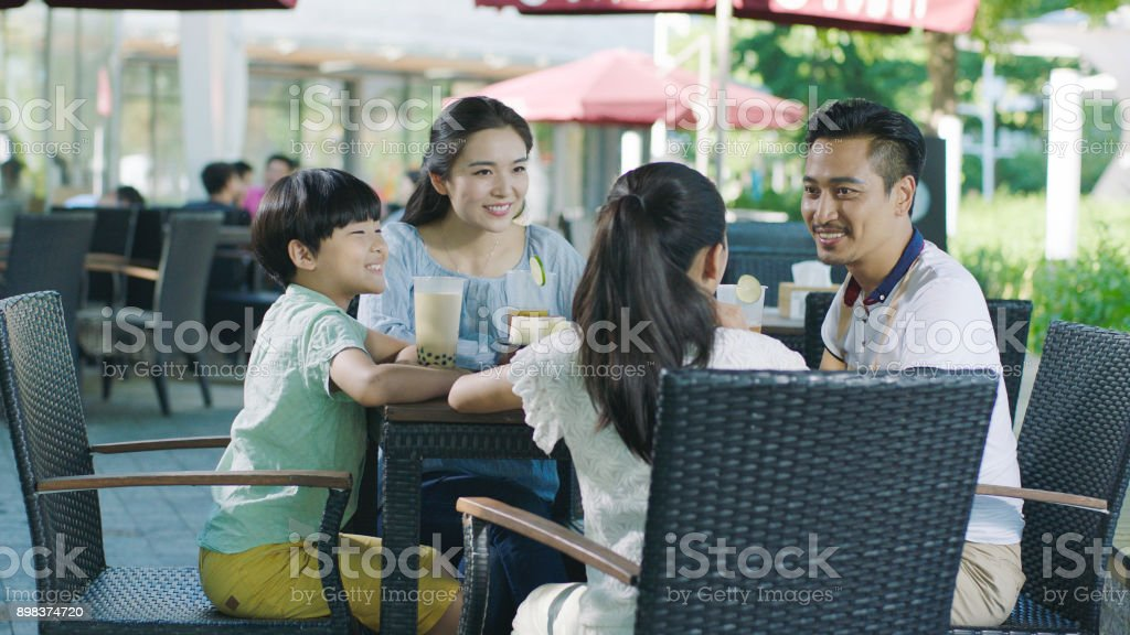 Chinese parents & kids taking break and enjoying drinks at outdoor cafe seat stock photo