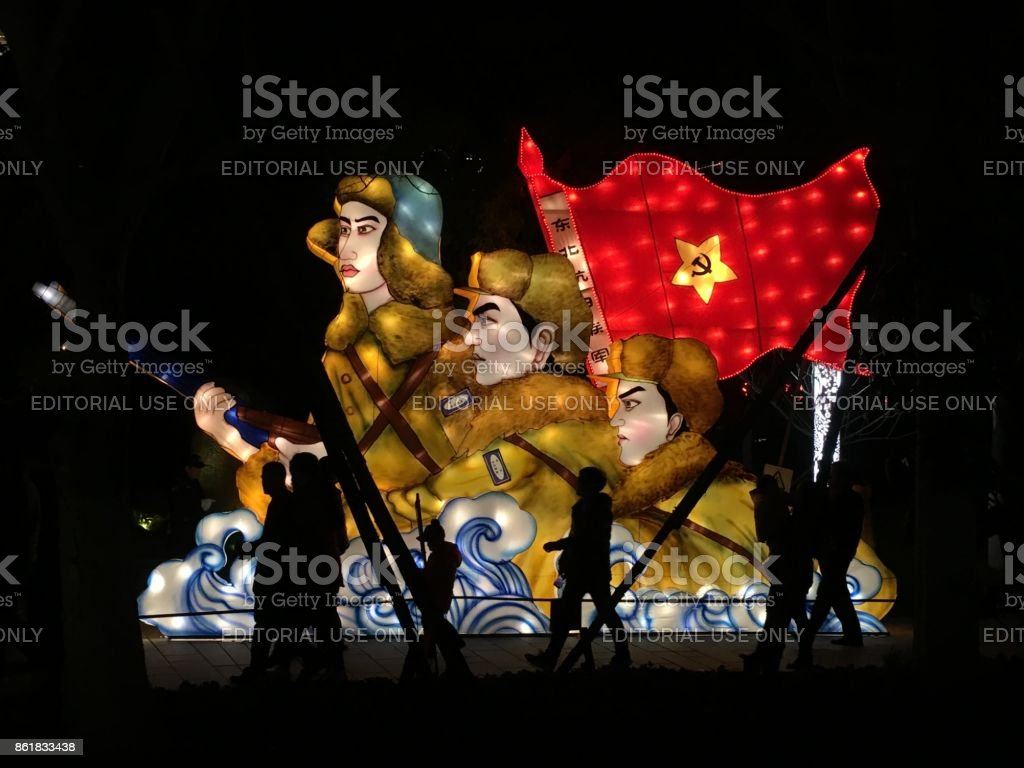 Chinese people walking in front of an illuminated communism sign lantern China stock photo