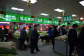 Beijing, China- April, 05, 2020: Chinese people wear protective masks shopping for food in a wet market, Beijing is reopening and backing to normal life