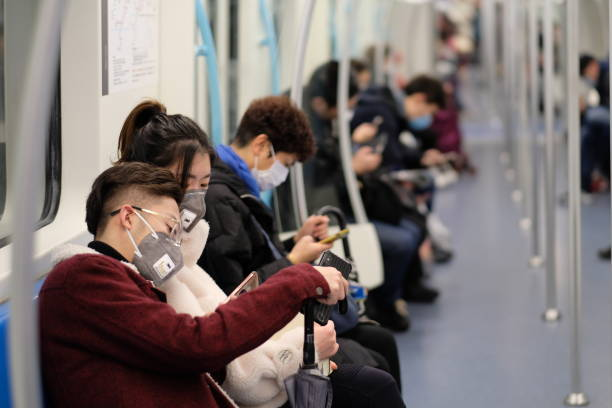 Chinese people wearing surgical mask sitting in subway Shanghai/China-Jan.2020: New type coronavirus pneumonia in Wuhan has been spreading into Shanghai. People wearing surgical mask sitting in subway in Shanghai medium shot stock pictures, royalty-free photos & images