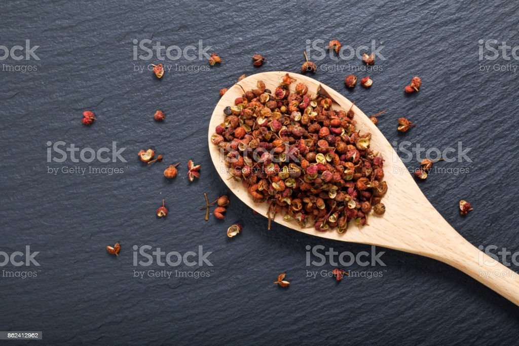 Chinese pepper, Sichuan pepper in wooden spoon on black slate stone plate with copy space stock photo