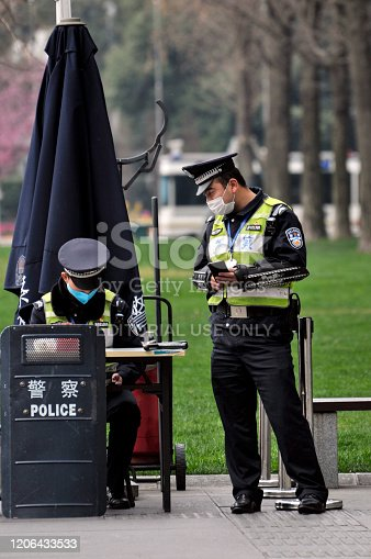Chengdu/China-Feb.2020: New type coronavirus pneumonia in Wuhan has been spreading into many cities in China.Chinese polices wearing masks are on duty in the Tianfu Square, Chengdu ,China,which is Chengdu's most famous place.