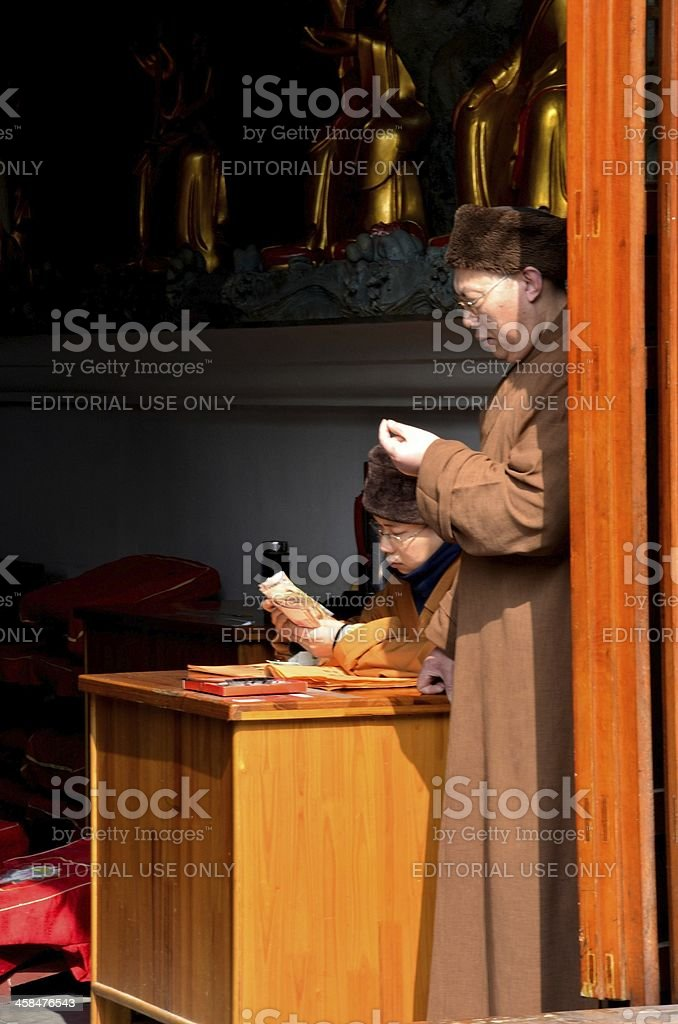 Chinese priests count donations at Shanghai temple royalty-free stock photo