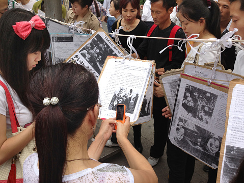 Xi'an, China - September 15, 2012: Chinese students and protestors use mobile phones to photograph and share anti-Japanese posters during Chinese demonstrations against Japan's purchase of the Diaoyu Islands.