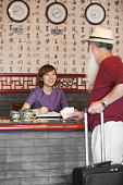 Chinese receptionist and guest at hotel front desk