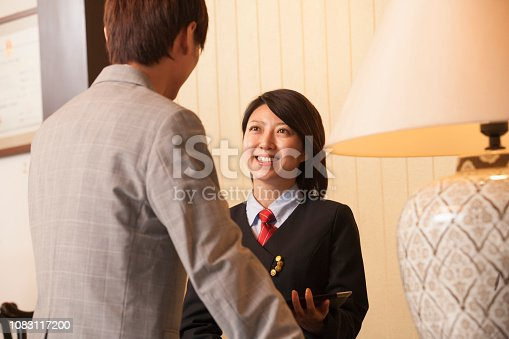 istock Chinese receptionist with client in hotel lobby 1083117200