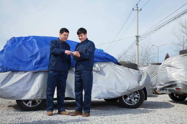 chinesische handwerker neben zerstört auto - plane kaufen stock-fotos und bilder