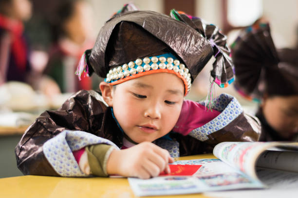 Chinese School Classroom Dong People Boy Learning with Book stock photo