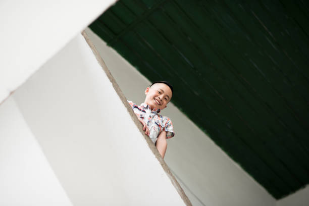 Chinese schoolboy smiling happy looking down stairway stock photo