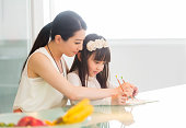 A Chinese woman and a girl work on schoolwork.