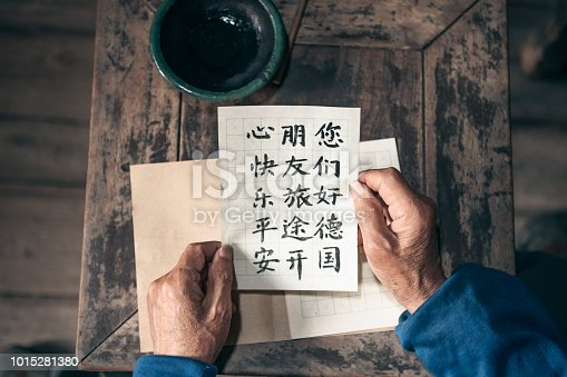 close up of old hands holding  paper with chinese calligraphy characters