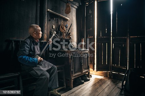 chinese senior man playing longneck lute in wooden house in daxu ancient town