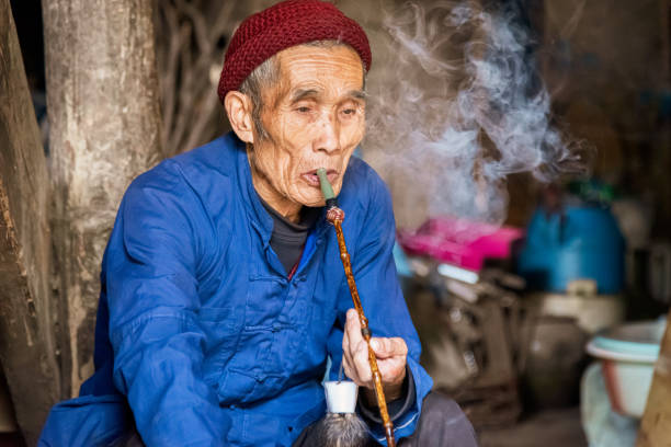 Chinese senior man smoking pipe in his home stock photo