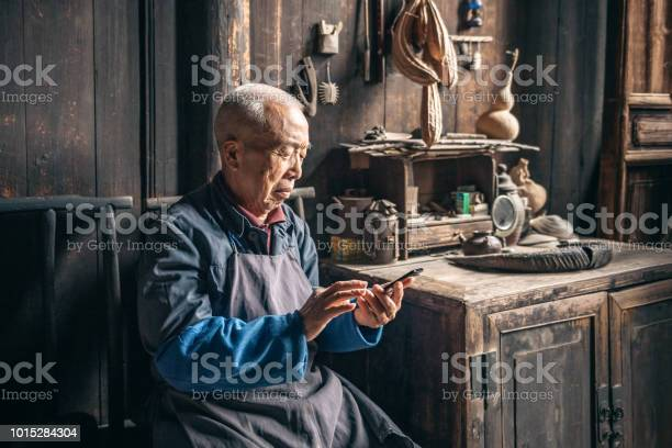 Chinese senior man tapping on mobile in wooden house picture id1015284304?b=1&k=6&m=1015284304&s=612x612&h=x4vf35q6xm5nhgaomogs9xcrallfefz1yymi ud ene=