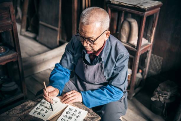 chinesischer senior Mann schreiben Kalligraphie Zeichen auf Papier – Foto