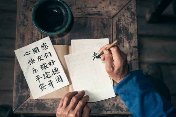 chinese senior man writing chinese calligraphy characters on paper - cultura cinese foto e immagini stock