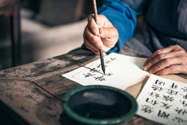 chinese senior man writing chinese calligraphy characters on paper stock photo