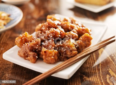 chinese sesame chicken with chopsticks , shot with selective focus.