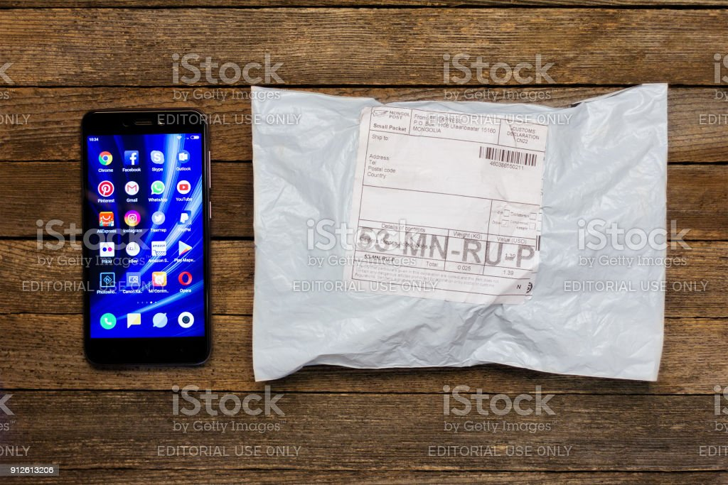 Adygea, Russia - January 24, 2018: Chinese smartphone xiaomi and parcel of the online store on a wooden table stock photo