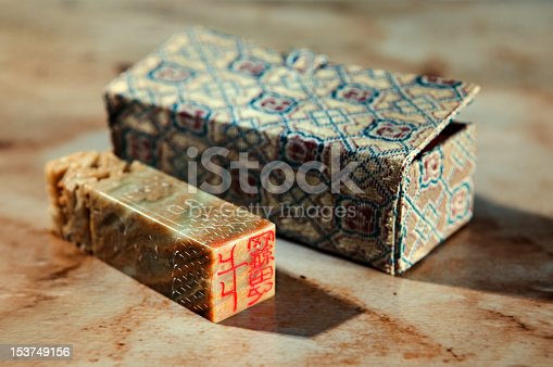 Close-up studio shot of a chinese stone stamp with its box. Selective focus.