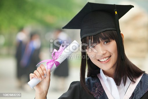 865186916 istock photo Chinese student in graduation cap and gown holding diploma 1082683220