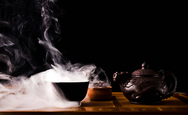 Chinese tea ceremony. Chinese tea ceremony. Ceramic tea pot and cups with the famous chinese puerh tea with vapour on a black background. tea room stock pictures, royalty-free photos & images