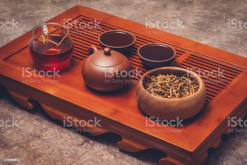 Chinese tea in Yixing clay teapot with teaware stand on tea tray Yixing clay teapot with clay tea cups, cha hai and wooden bowl stand on tea tray. Asia Stock Photo