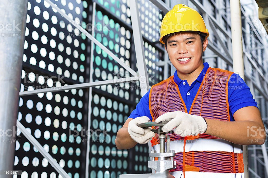 Chinese Technician working on valve royalty-free stock photo