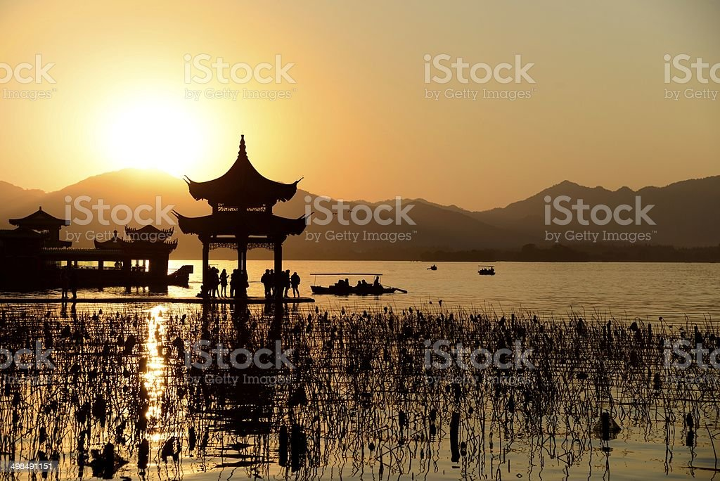 Chinese temple in west lake with sunset stock photo