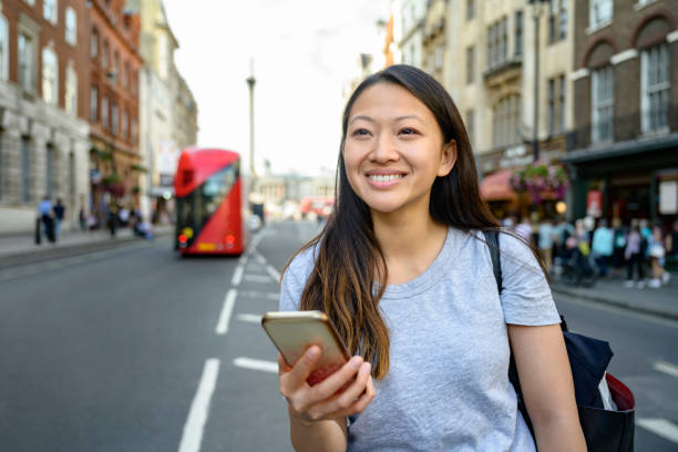 Chinese tourist in London checking smart phone for guidance Independent young Chinese woman using smart phone for sightseeing tips while vacationing in London. central london stock pictures, royalty-free photos & images