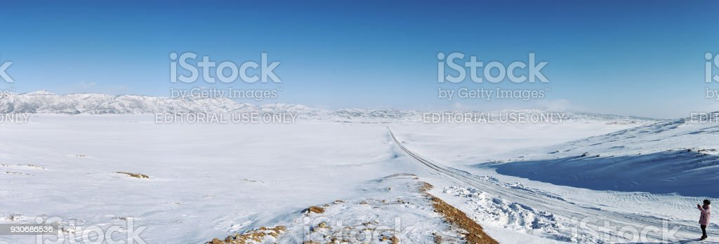 Chinese tourist taking pictures of a grassland covered in ice and snow in Xinjiang, northen China stock photo