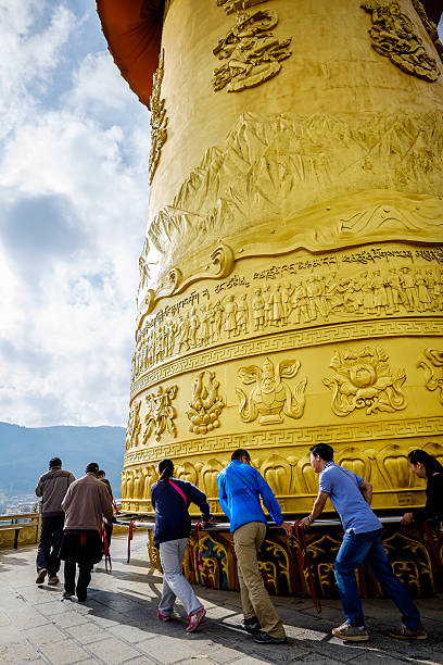 Chinese tourists turning a golden prayer wheel in Shangrila stock photo