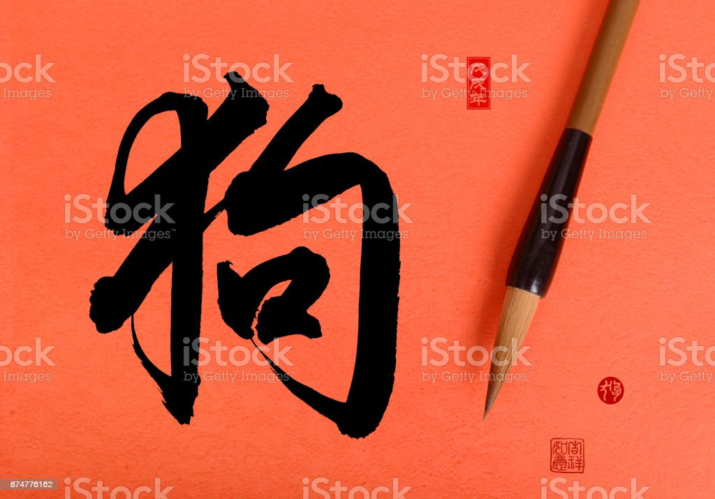 Chinese traditional brush with calligraphy meaning:dog,red stamps mean: good bless for new year stock photo
