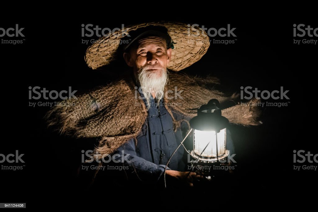 Chinese Traditional Fisherman Portrait Li River China Traditional chinese Senior Fisherman (75 years) in his traditional clothes at night in the dark only illuminated from his petroleum lamp. Xing Ping, close to the city of Yangshuo County, Guangxi, Guilin, China 70-79 Years Stock Photo