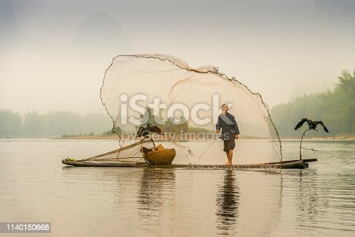 Traditional Chinese 75 year old senior fisherman in traditional clothes and bamboo hat on his wooden fishing raft with two cormorants fishing with a net on the Li River in the early morning fog light at sunrise. Shot at Xing Ping, close to the city of Yangshuo County, Guangxi, Guilin, China.